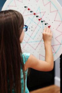 girl using peg board to improve focus