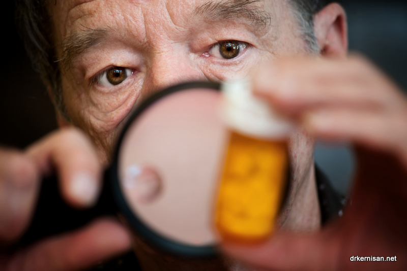 Older man reading label of medicine bottle using magnifying glass