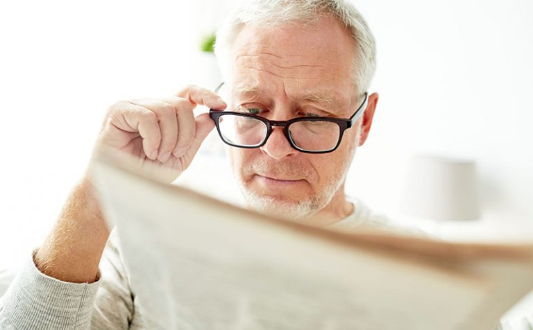 Older man with glasses reading newspaper